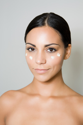 Young woman with moisturizer on face